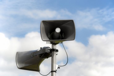 Two loudspeakers attached to pole. Cloudy sky on background. Clipping path included, making isolation easy.